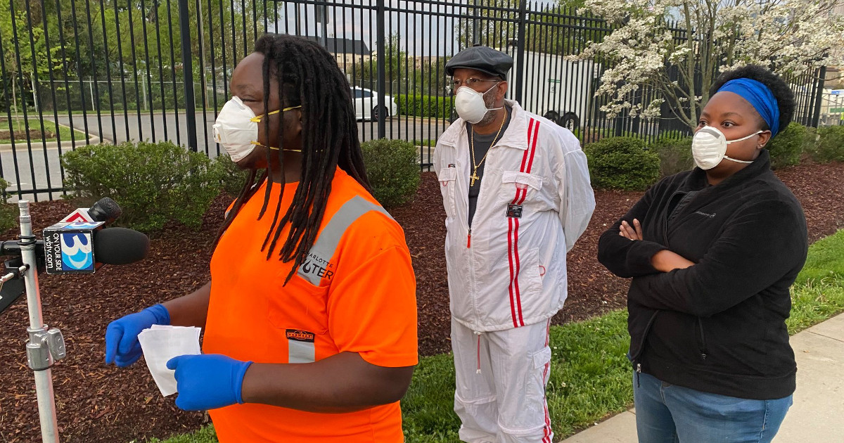 Three workers wearing masks and practicing social distancing speak at press conference