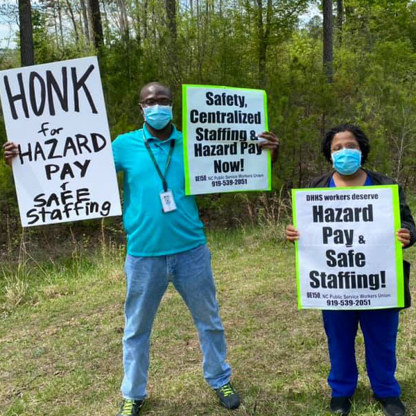 Workers with signs reading Honk for Hazard Pay and Safe Staffing