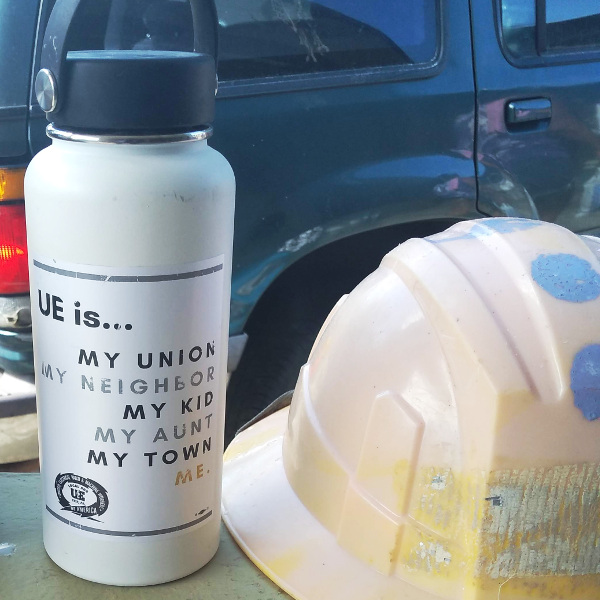 "Photo of water bottle with sticker reading ""UE is... my union, my neighbor, my kid, my aunt, my town, me."" and a UE Local 506 logo. Next to the water bottle is a hard hat."