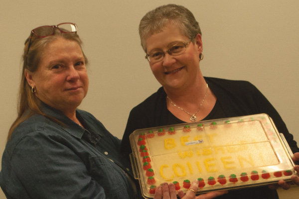 "Charlene Winchell presents cake to Colleen Bochmann. Writing on cake reads ""Best wishes Colleen!"""