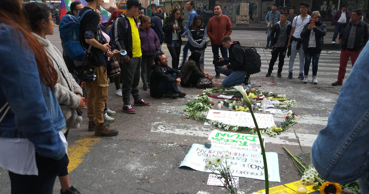 A group of people gathered around a memorial of signs and flowers laid out on a street