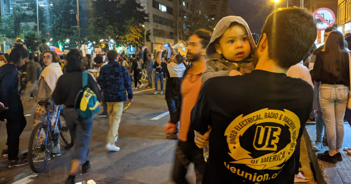 Crowd in the street at night. At right front of the photo, a young man holds a baby. His back is to the camera, displaying a t-shirt with a large UE logo on it.
