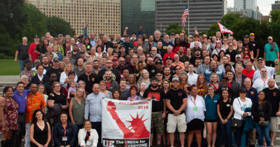 "Photo of UE convention delegates and guests with a banner with a statue-of-liberty image and the text ""76th"" ""Pittsburgh 2019"" and ""UE: The Union for Everyone"""