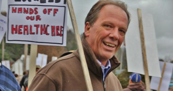 """Photo of UE President Peter Knowlton with a picket sign that says """"Hands off our healthcare"""""""