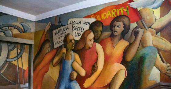 Mural of workers with red Solidarity flag and signs reading Huelga Contra la Injusticia and Down with Speed Up