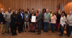 Rocky Mount Mayor David Combs presenting resolution honoring 1978 strikers to Marjorie Evans with others in attendance